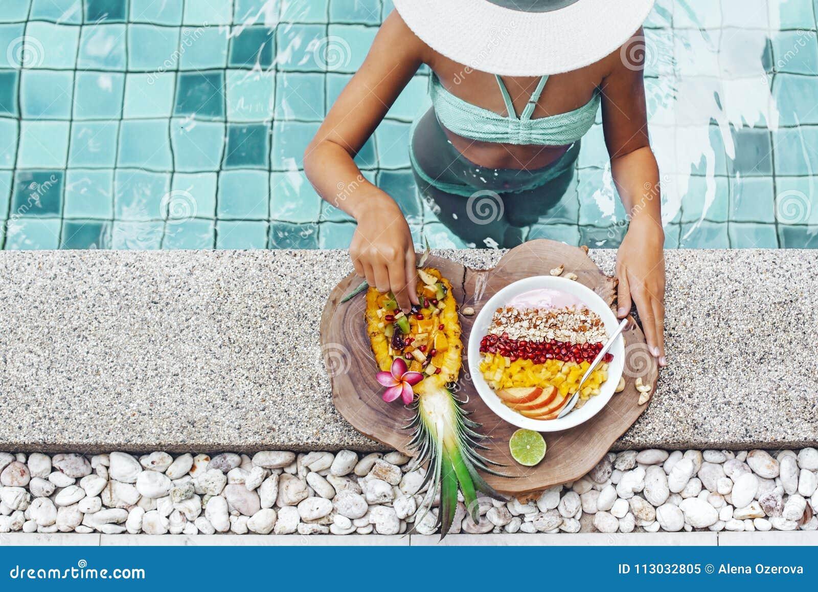 Muchacha que come las frutas exóticas en la piscina