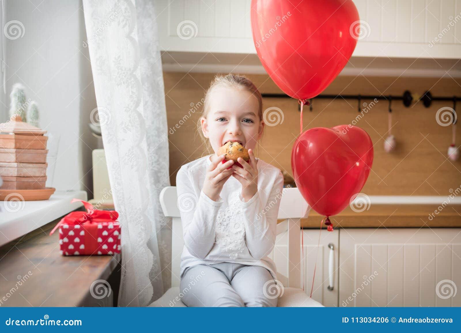 Muchacha que come su magdalena del cumpleaños en la cocina, rodeada por los globos