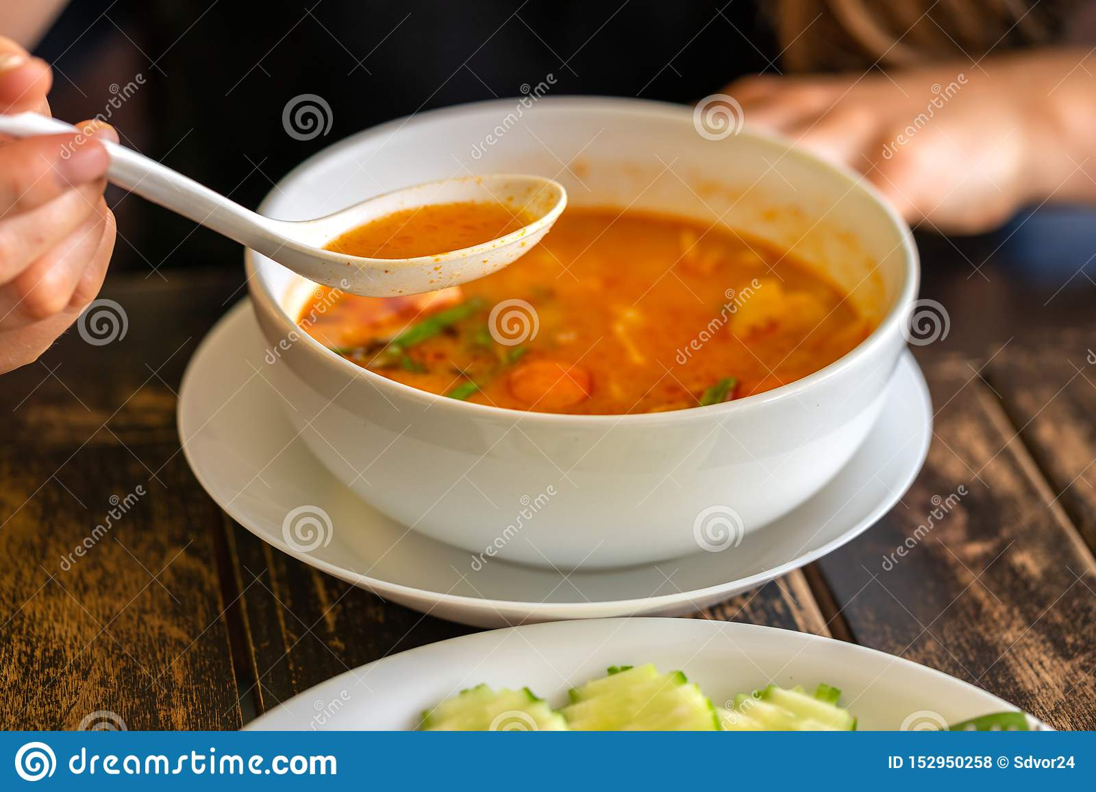 Muchacha que come a Tom Yam Kung, cocina tailandesa Cierre para arriba