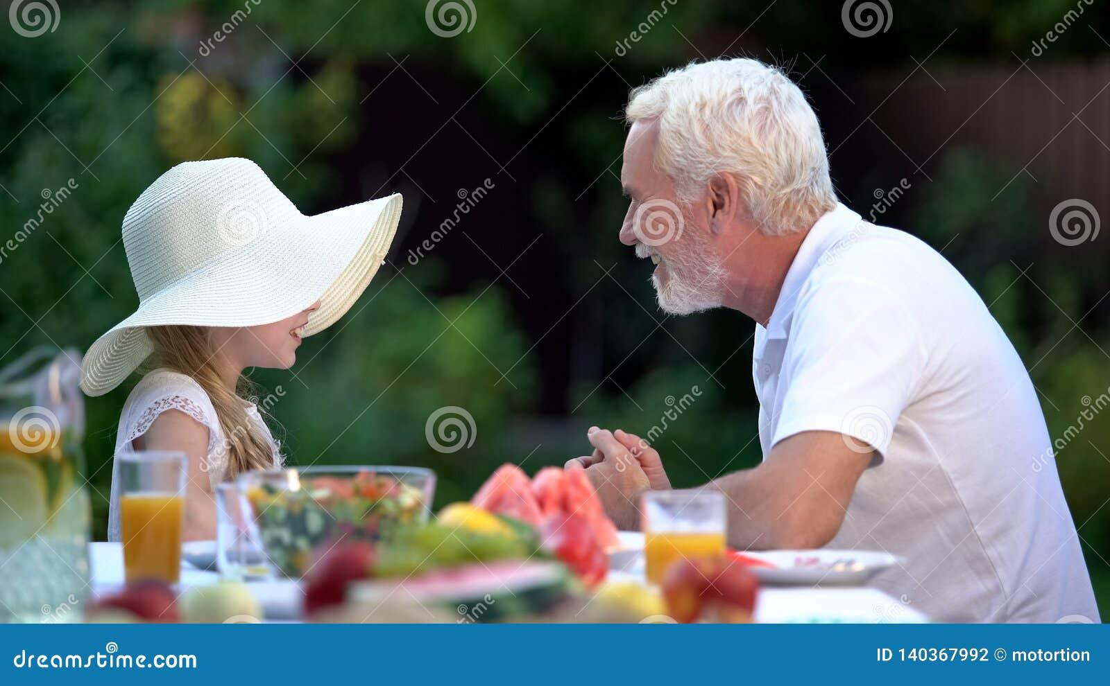 Muchacha que cuenta la historia emocionante al abuelo, tiempo del gasto junto, relación