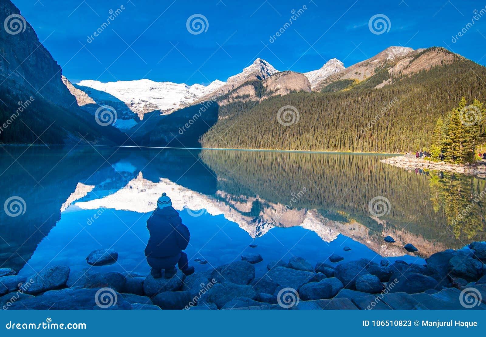 Muchacha que disfruta de la reflexión del árbol nevoso de la montaña y del árbol de hoja perenne en el agua de Lake Louise