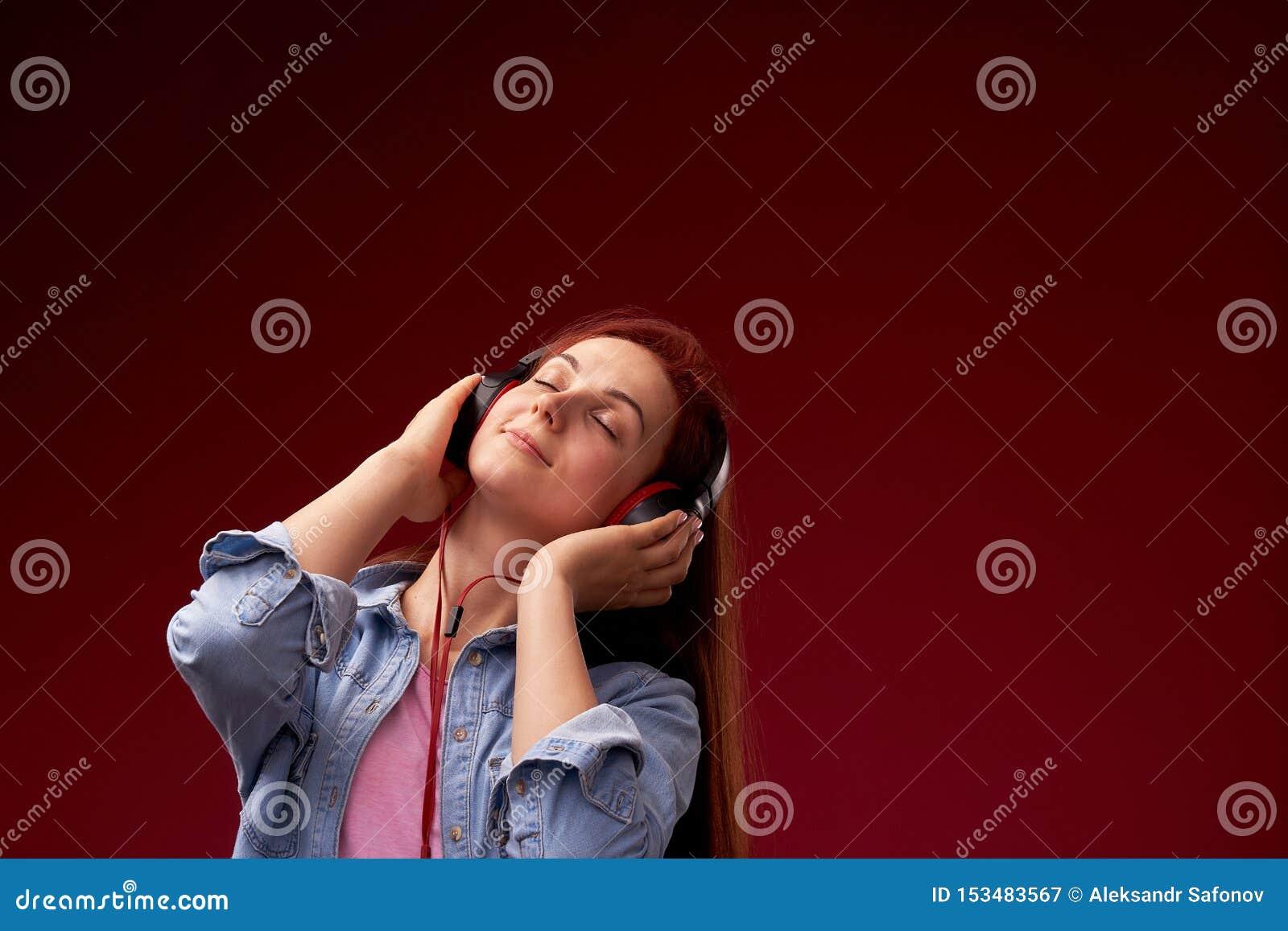 Muchacha que escucha la m?sica en auriculares muchacha hermosa joven pelirroja en vaqueros y la sonrisa feliz de la camiseta en a