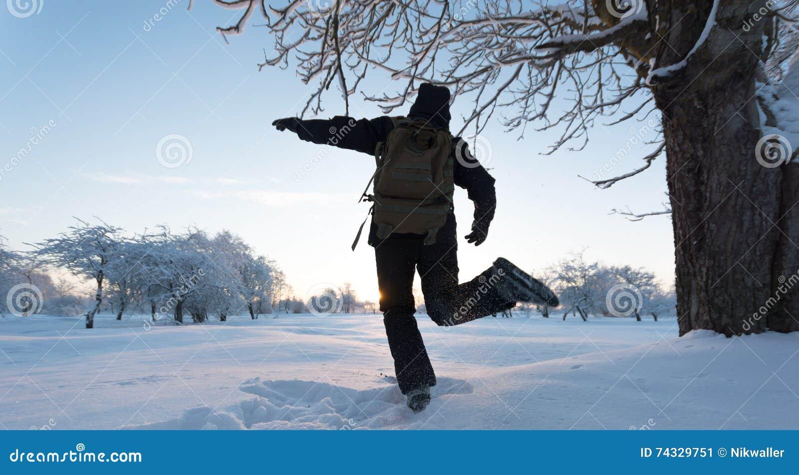Muchacha que golpea nieve con el pie Paisaje del invierno Puesta del sol