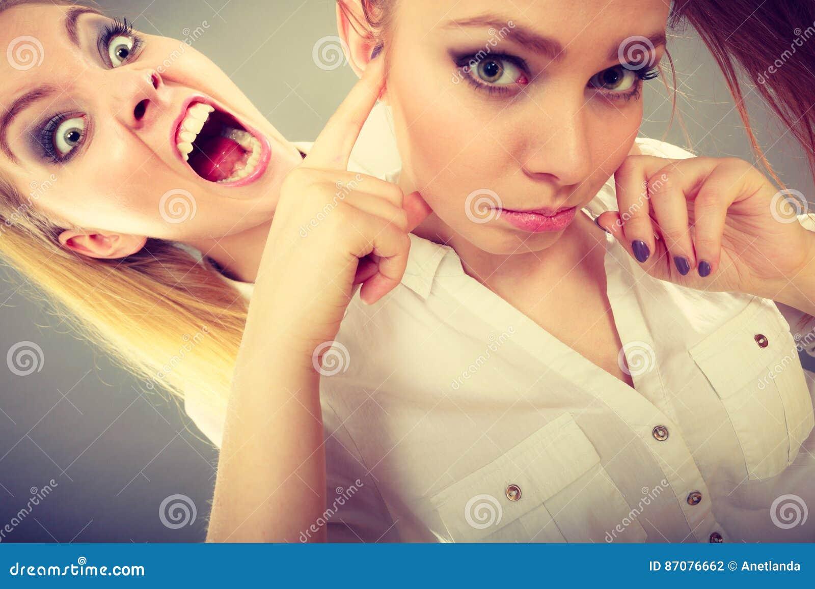 Muchacha que grita en su amigo, closing femenino de la furia sus oídos