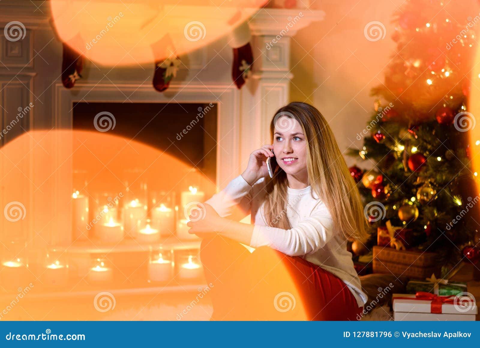 Muchacha que habla risueñamente en la sentada del teléfono