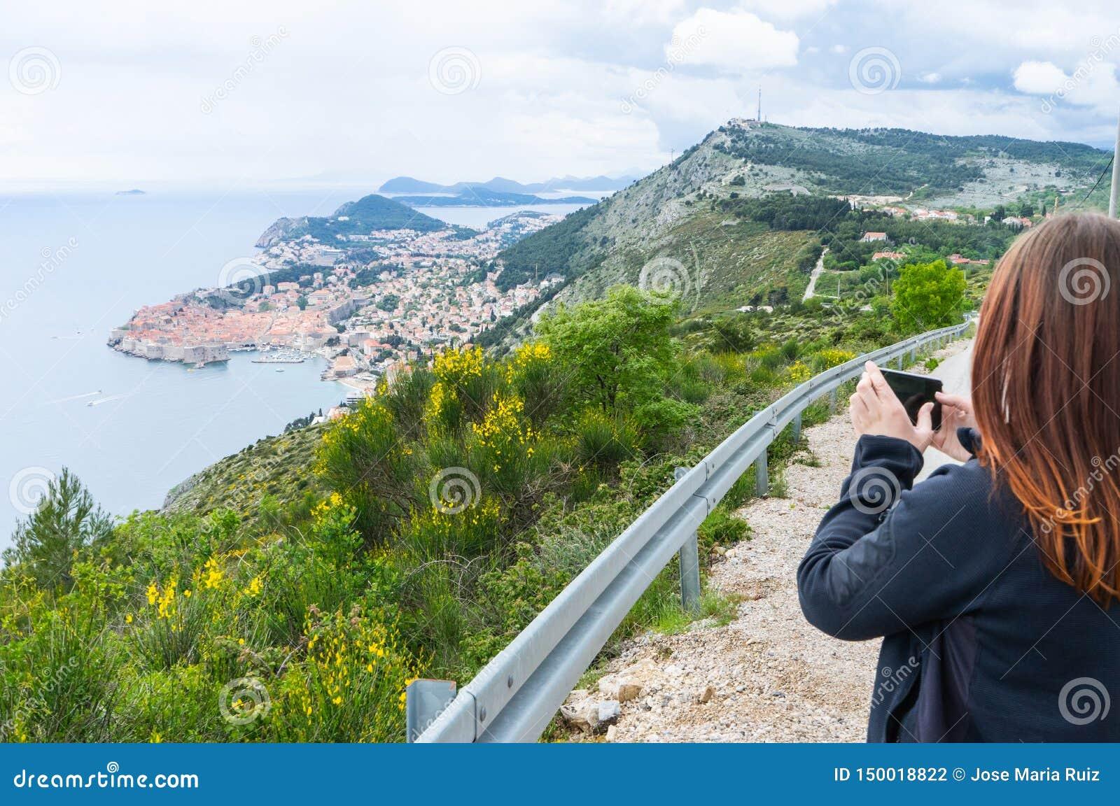 Muchacha que hace imágenes de Dubrovnik en la colina con un teléfono elegante en un pequeño camino a la ciudad vieja en Croacia