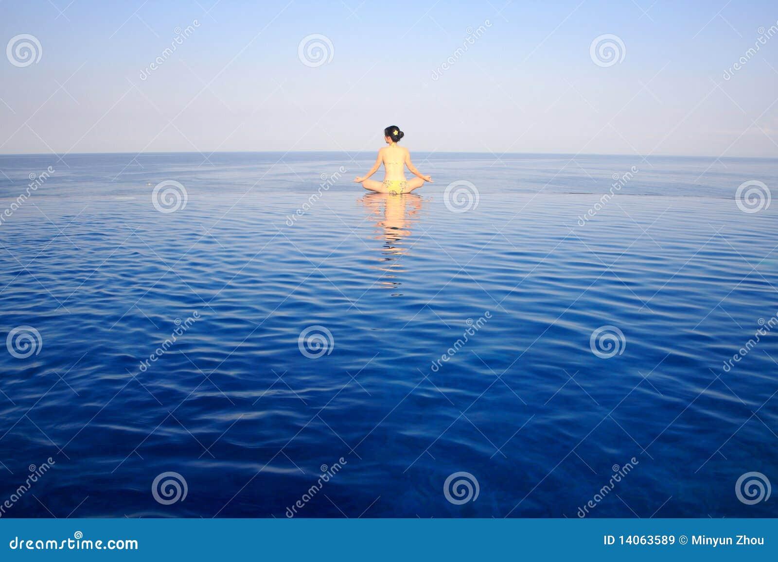 Muchacha que hace yoga con la opinión del mar