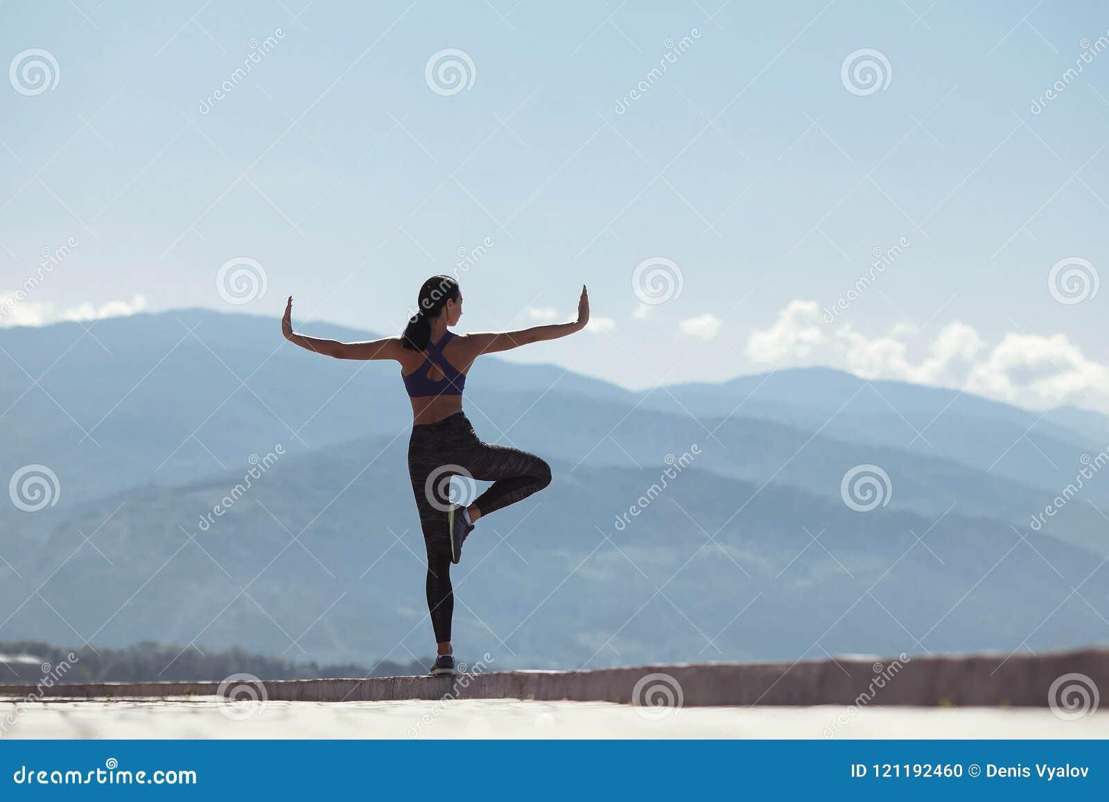 Muchacha que hace yoga por la mañana, en la costa por el mar