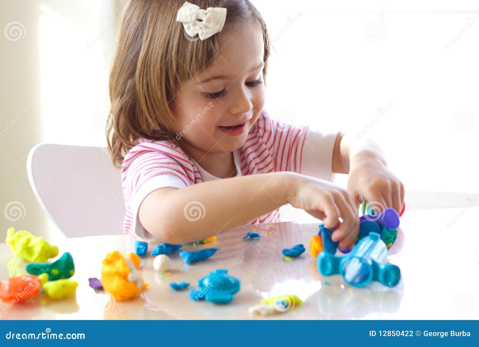 Muchacha que juega con pasta del juego