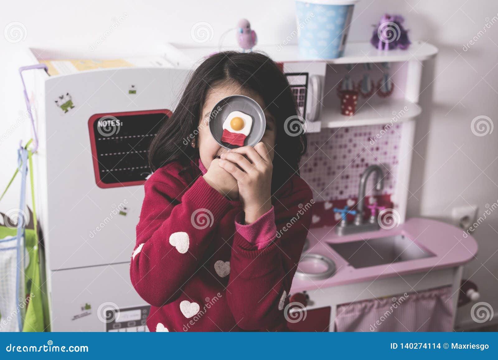 Muchacha que juega en cocina del juguete con el huevo frito falso
