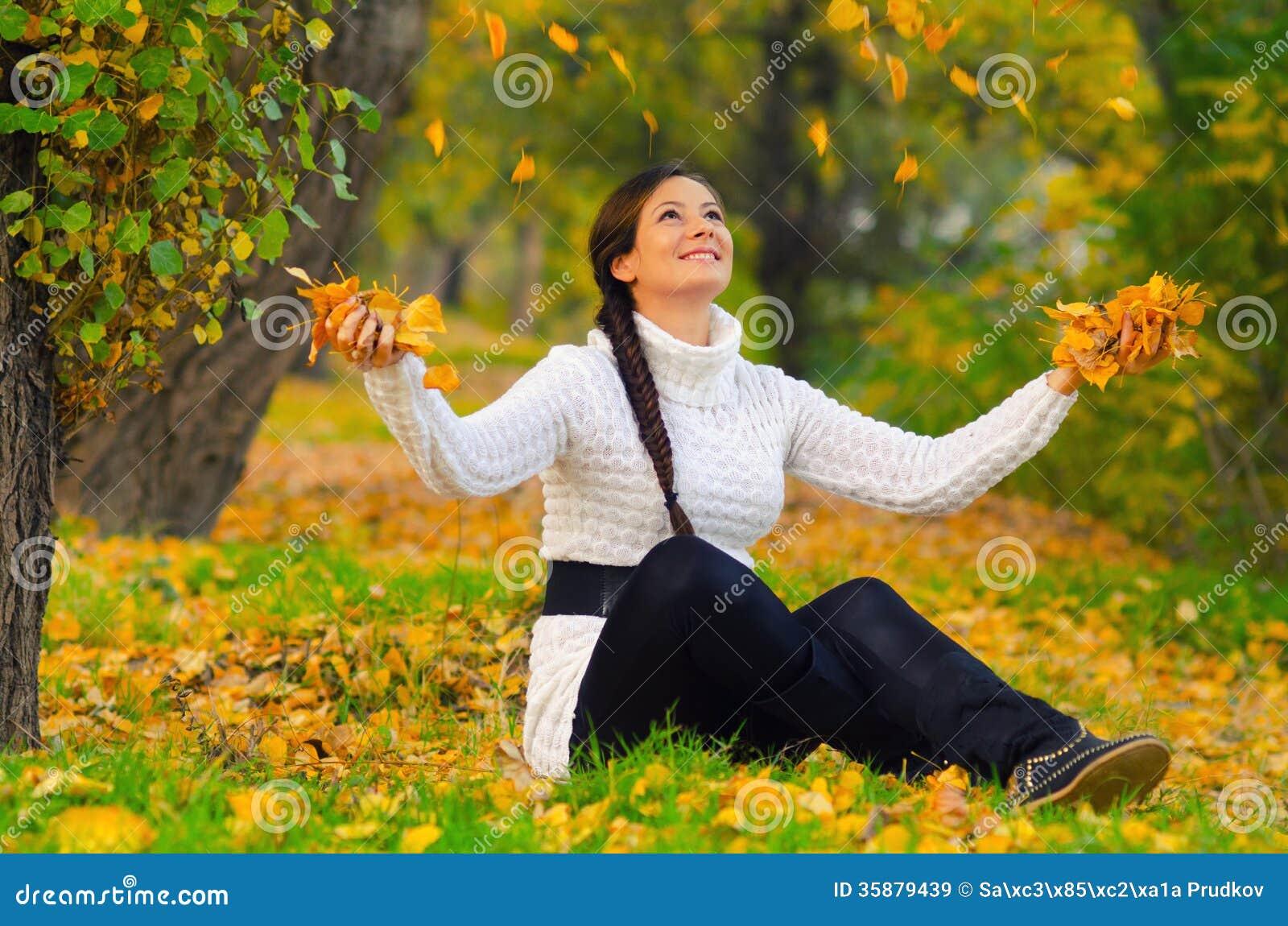 Muchacha que lanza las hojas de otoño secas en el aire