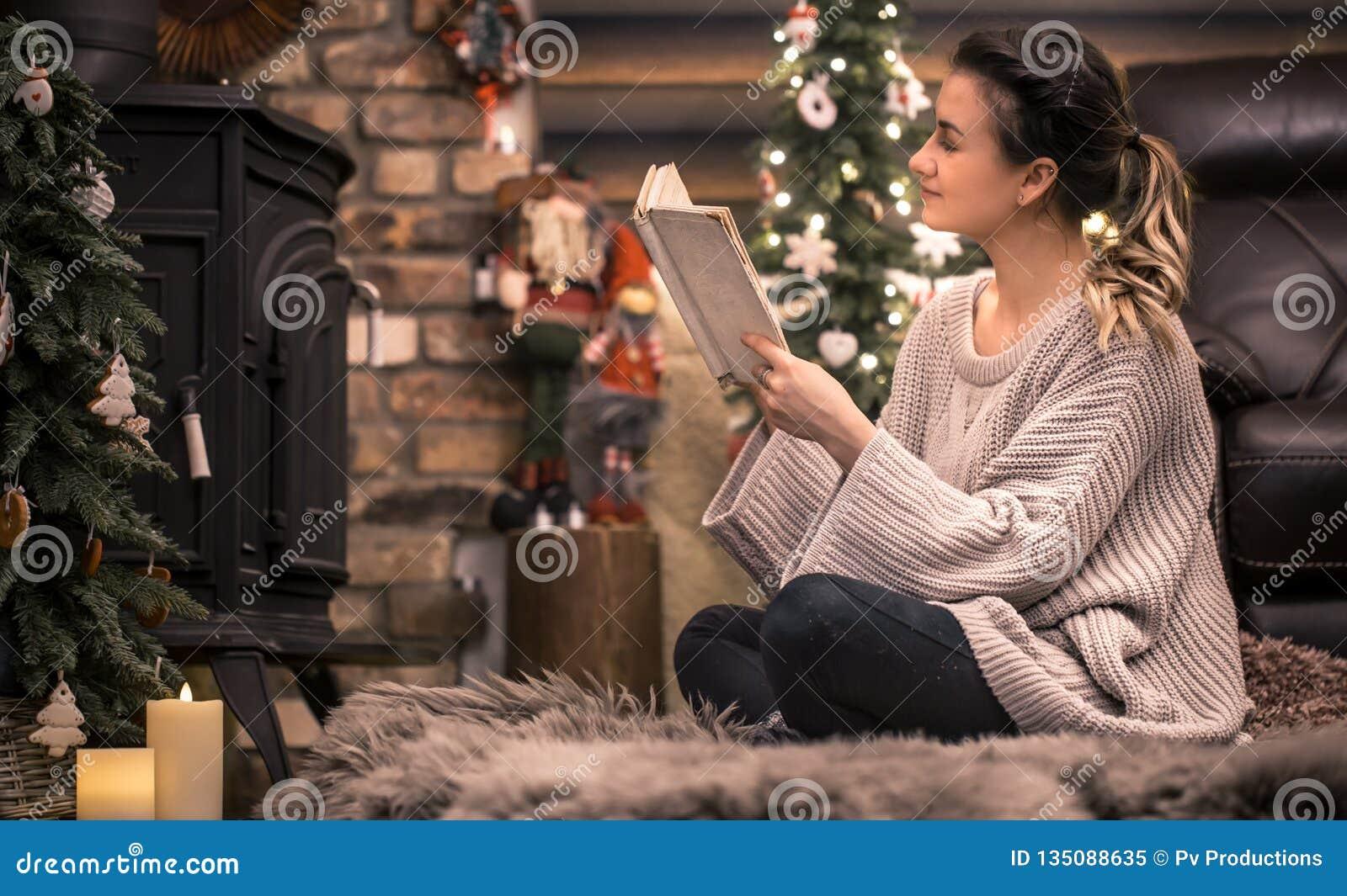 Muchacha que lee un libro en una atmósfera casera acogedora cerca de la chimenea
