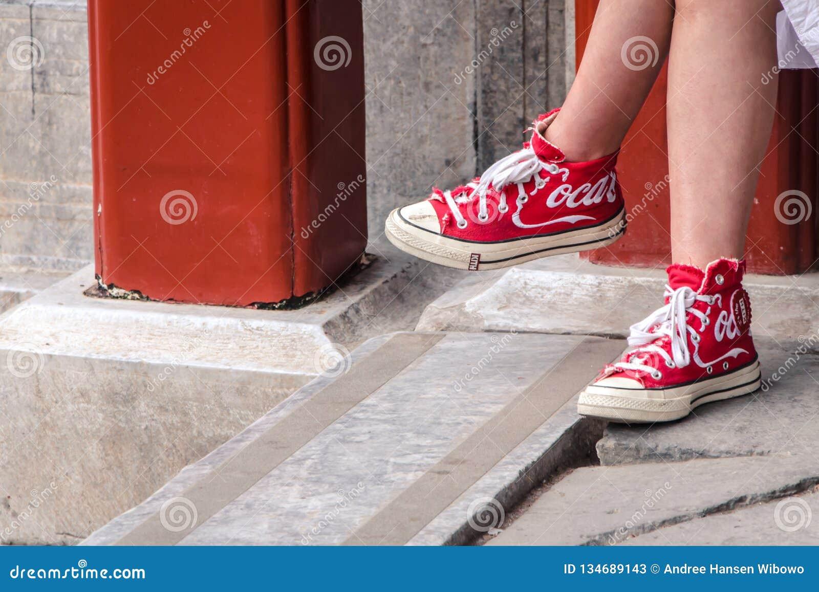 Muchacha que lleva los zapatos rojos con Coca Cola Logo en él