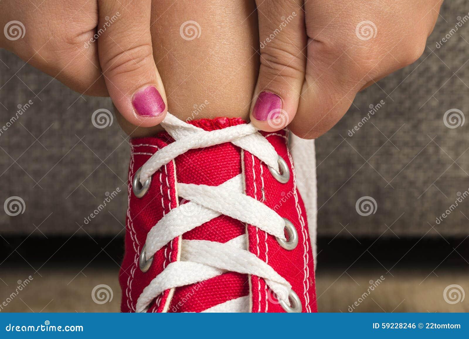 Muchacha que lleva un par de zapatillas de deporte rojas