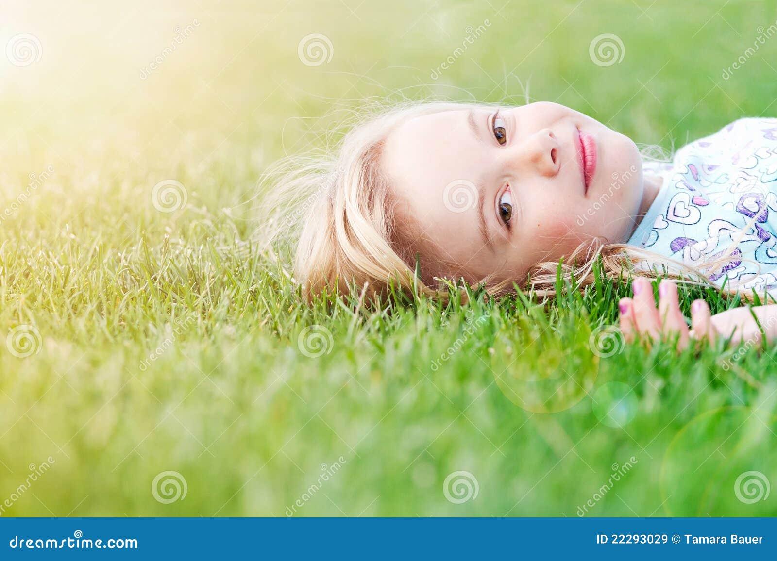 Muchacha que miente en hierba en resorte