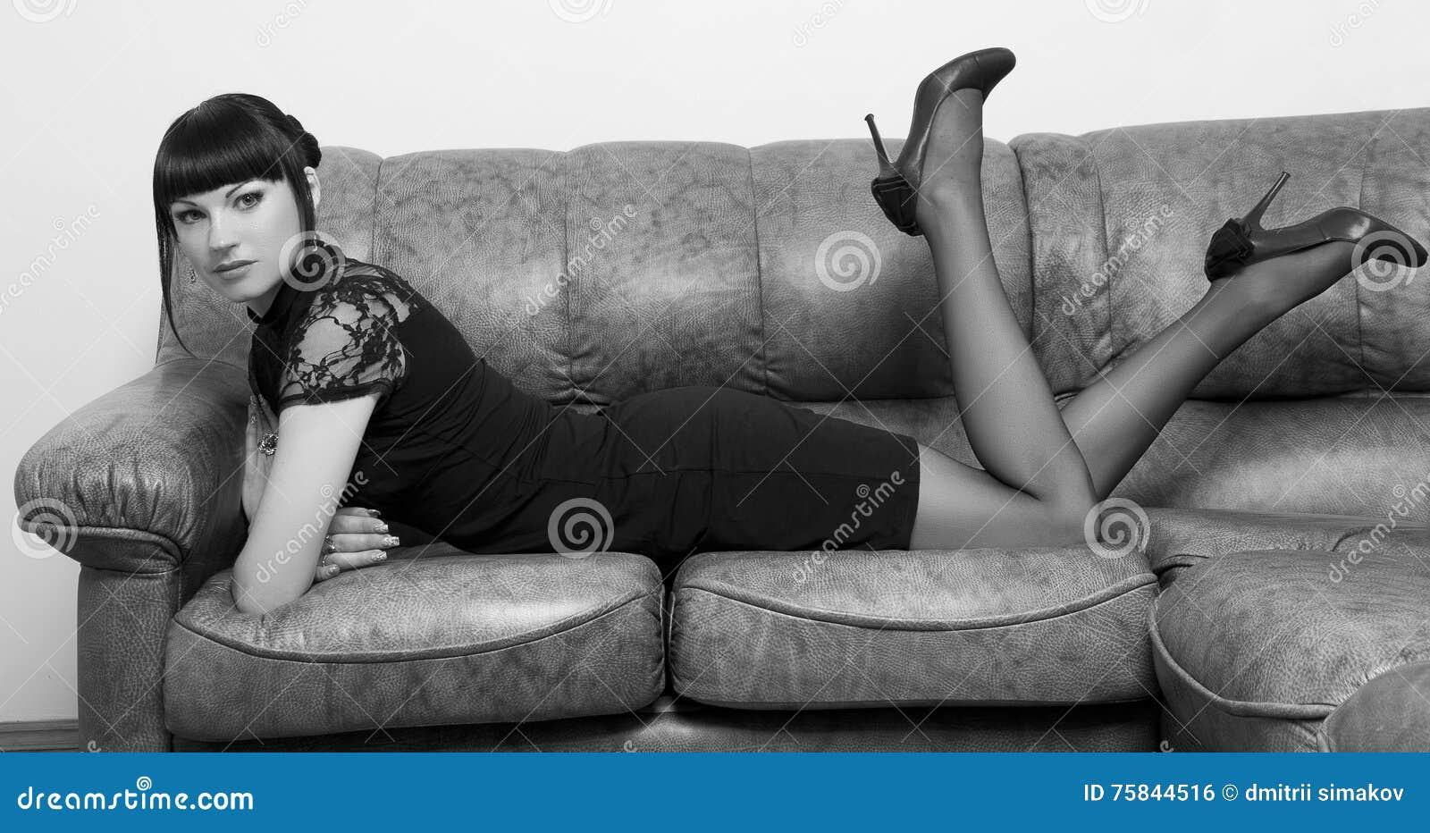 Muchacha que miente en un sofá en la oficina