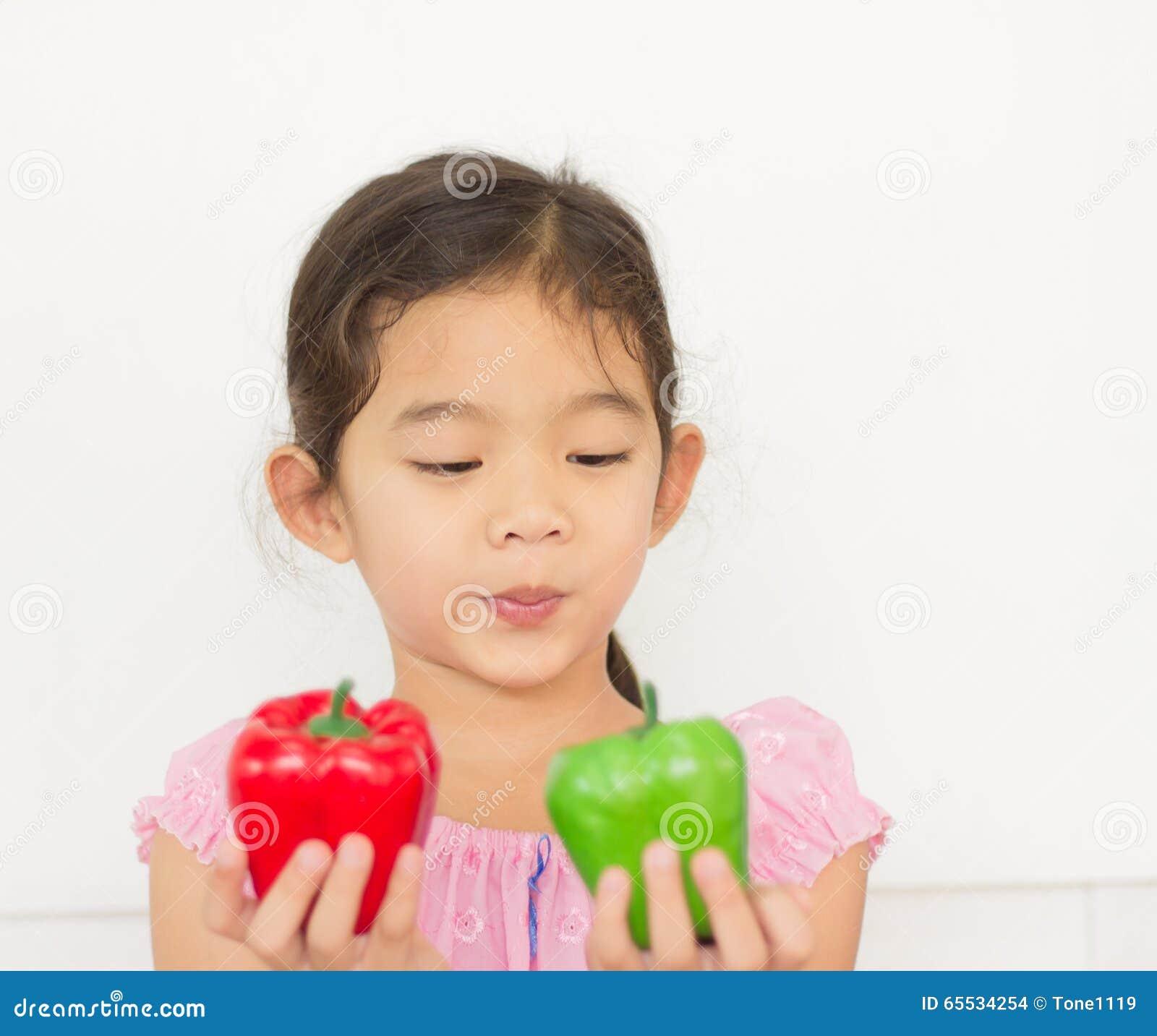 Muchacha que mira la fruta del paprika en su mano