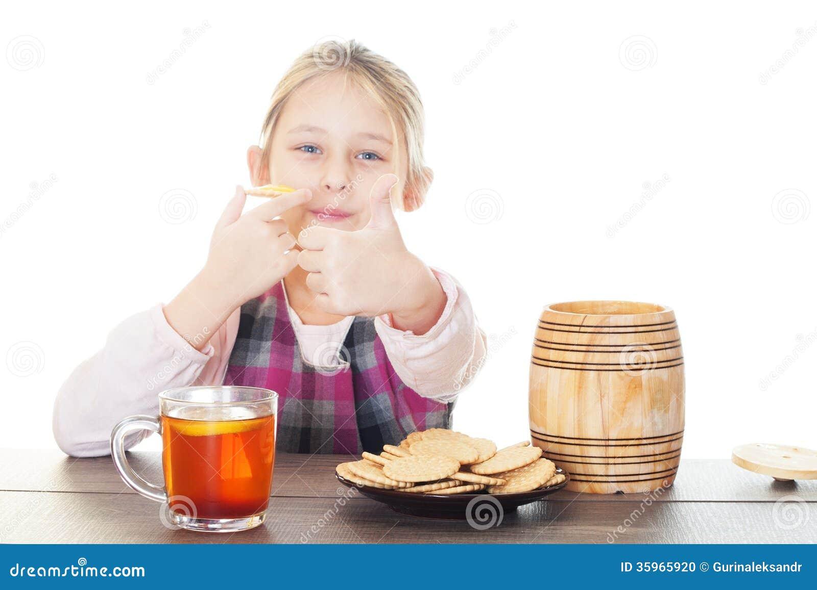 Muchacha que muestra el pulgar y que come la miel