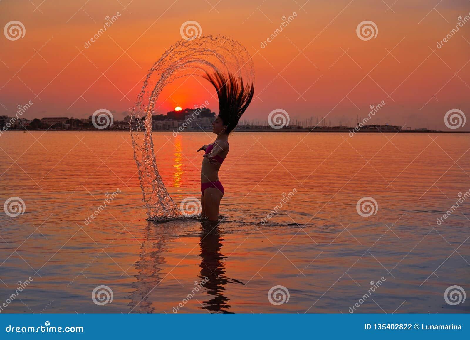 Muchacha que mueve de un tirón tirón del pelo en la playa de la puesta del sol