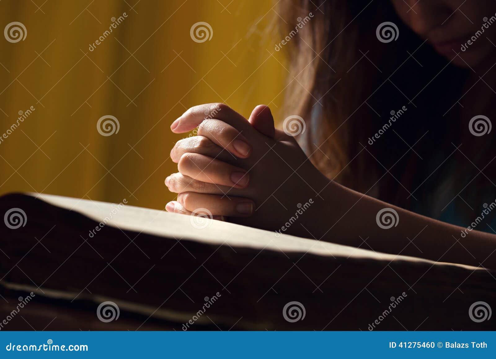 Muchacha que ruega con las manos en la biblia