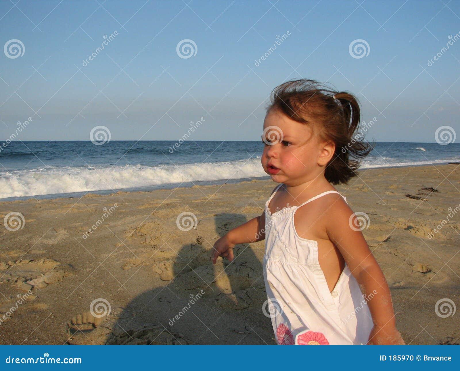 Muchacha que se ejecuta en la playa