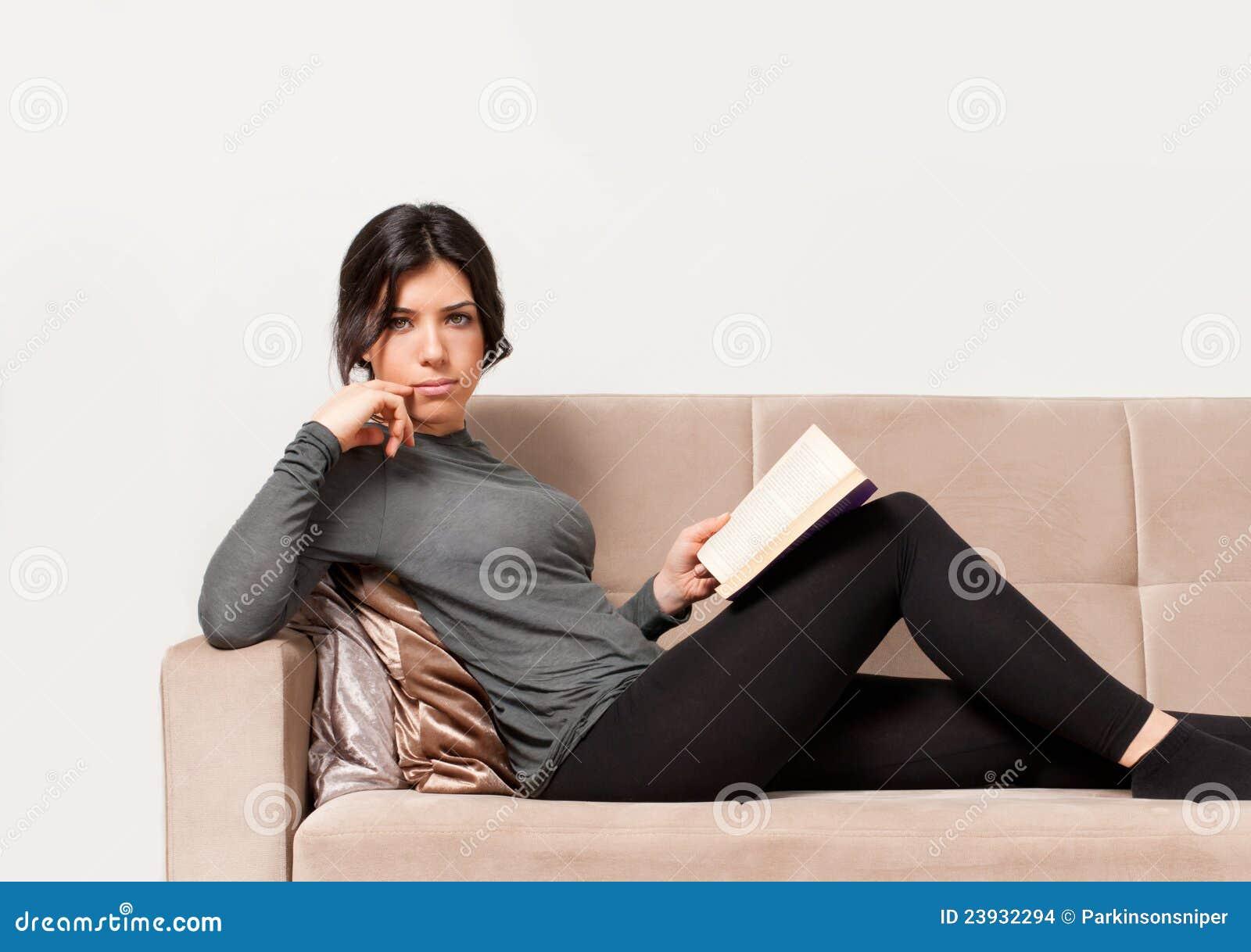 Muchacha que se reclina sobre el sofá