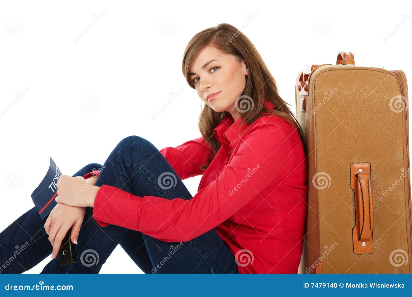 Muchacha que se sienta cerca de una maleta