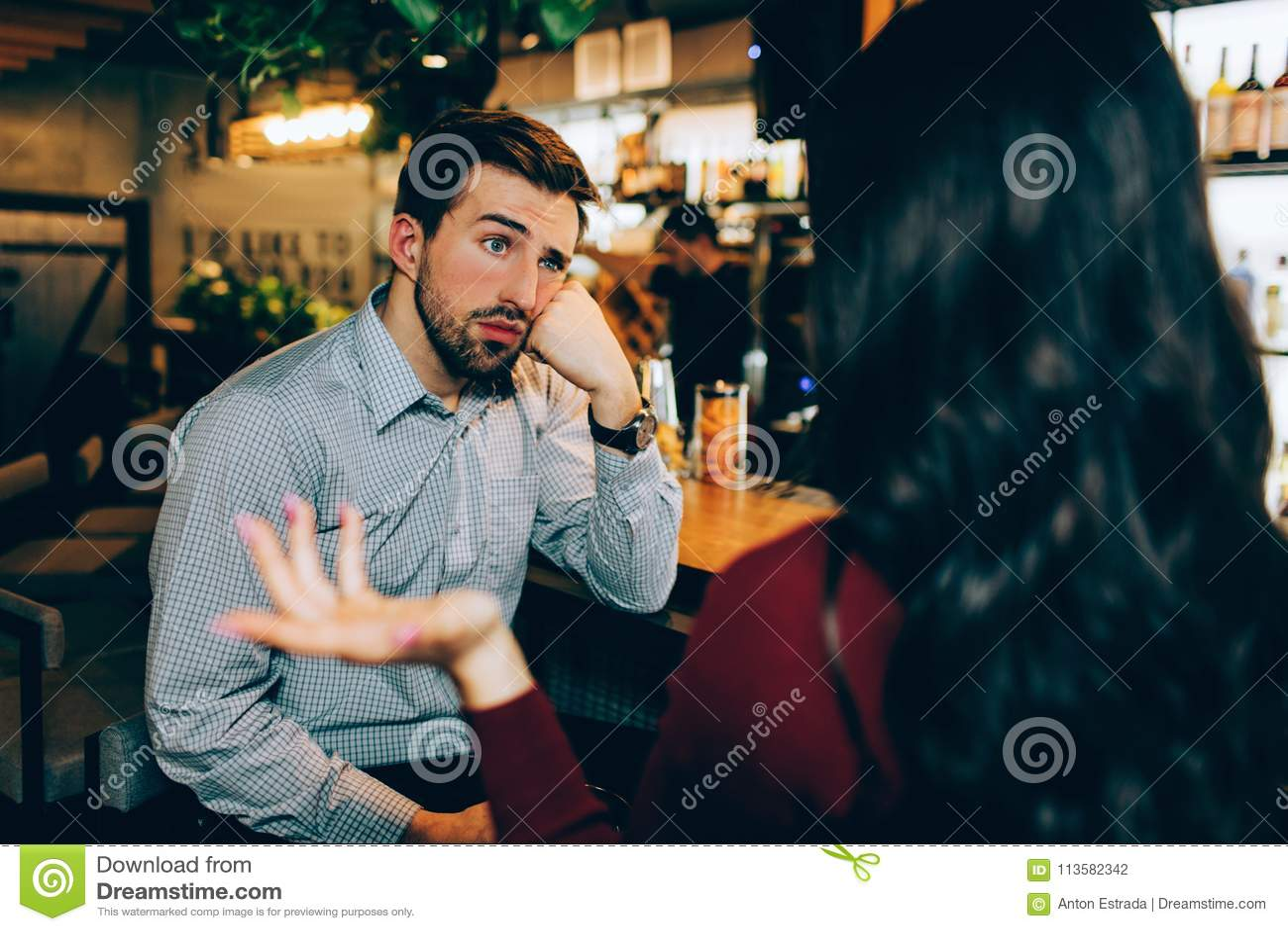 Muchacha que se sienta delante de individuo joven y que habla con él Él parece aburrido El hombre no está interesado en la conver