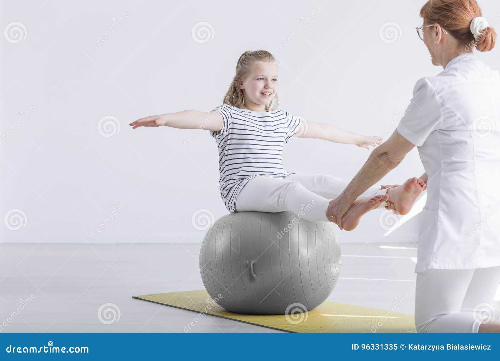 Muchacha que se sienta en bola del gimnasio