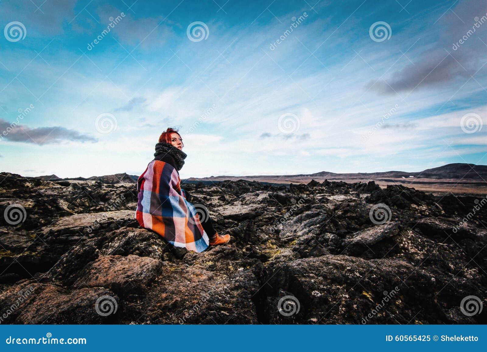 Muchacha que se sienta en el área volcánica de Krafla, Islandia