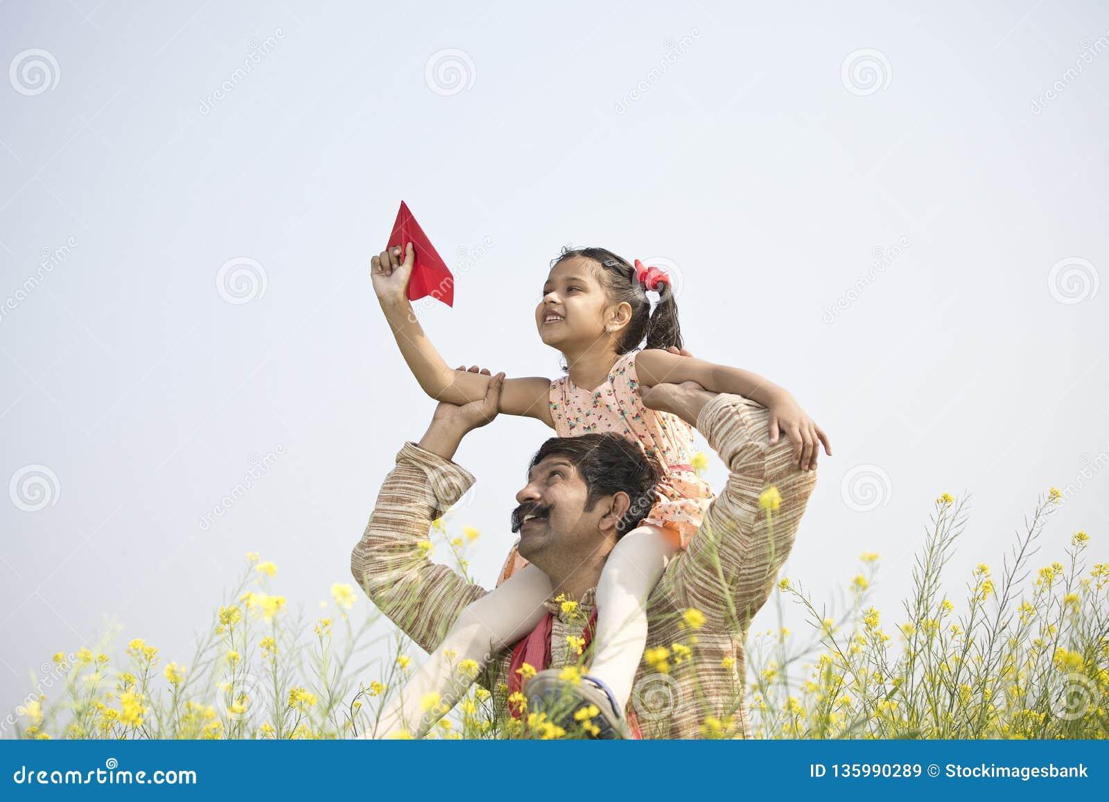 Muchacha que se sienta en el hombro y el aeroplano de papel que lanza del padre
