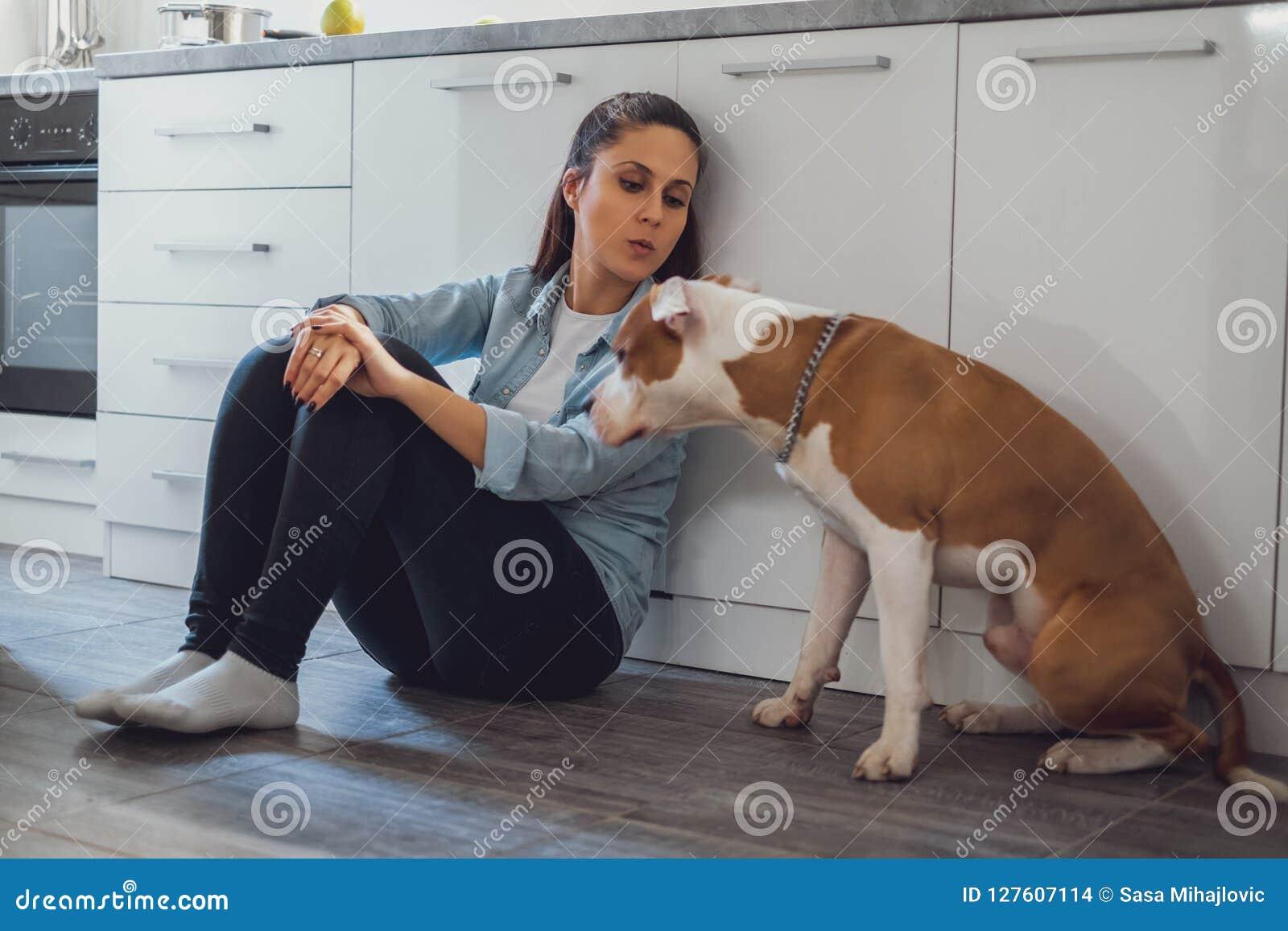 Muchacha que se sienta en el piso de la cocina que besa su perro