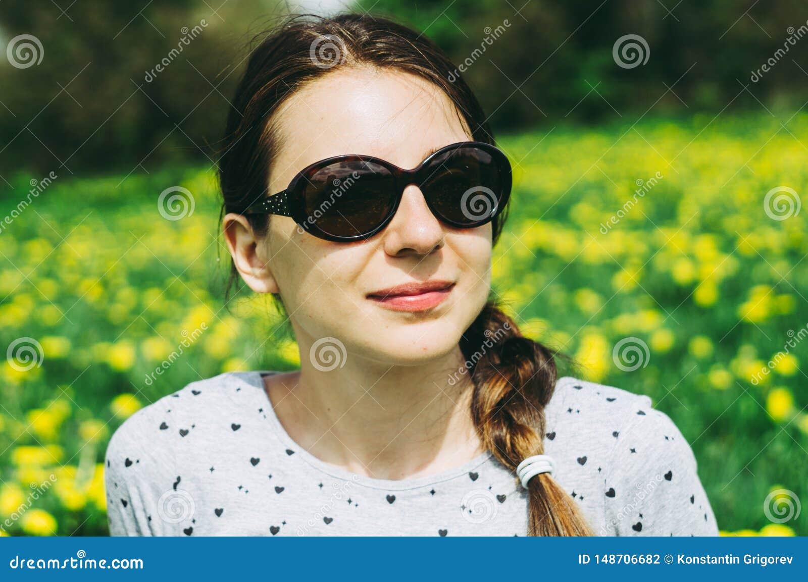 Muchacha que se sienta en el prado con los dientes de le?n amarillos