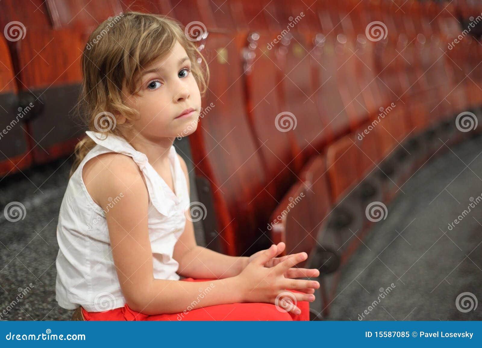 Muchacha que se sienta en la escalera cerca de las butacas en circo