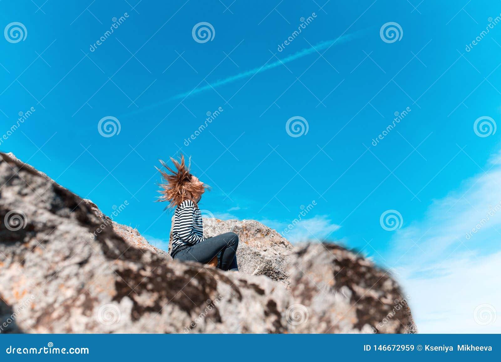 Muchacha que se sienta en un acantilado que pasa por alto el cielo con su soplar del pelo