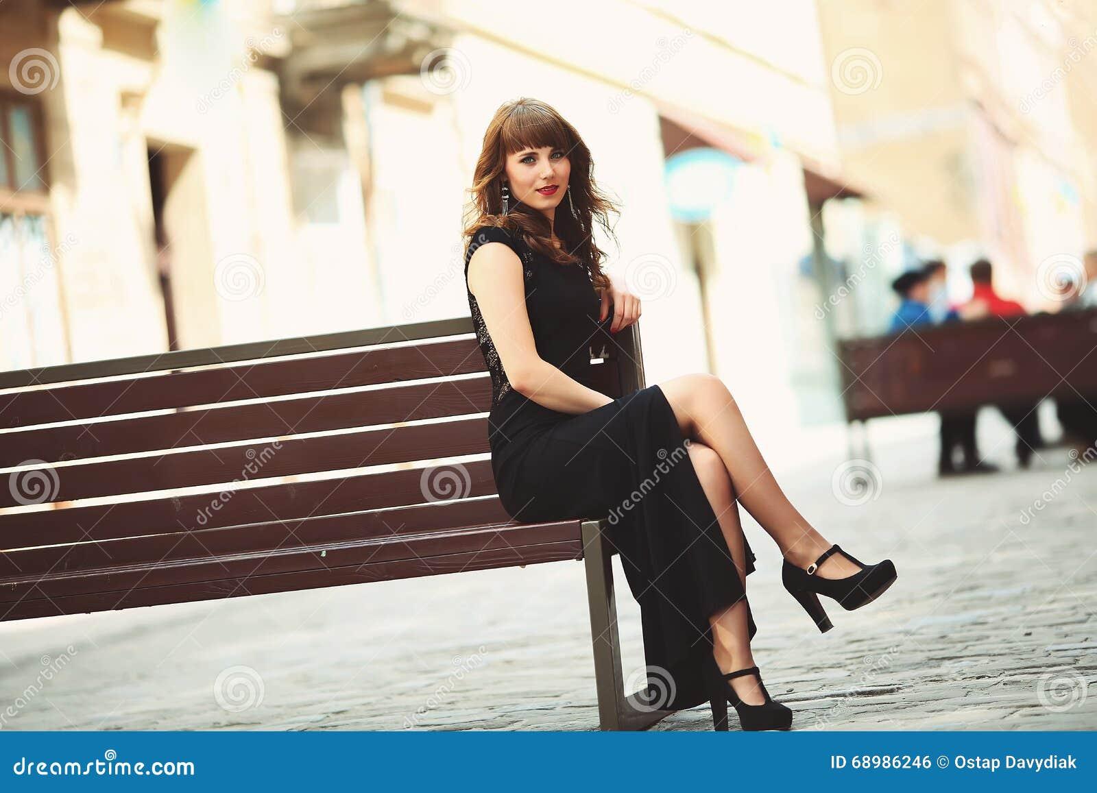Muchacha que se sienta en un banco en la ciudad