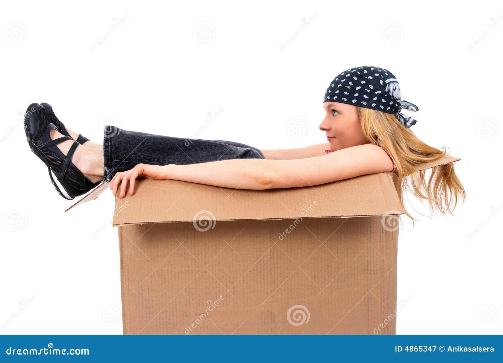 Muchacha que se sienta en una caja de cartón