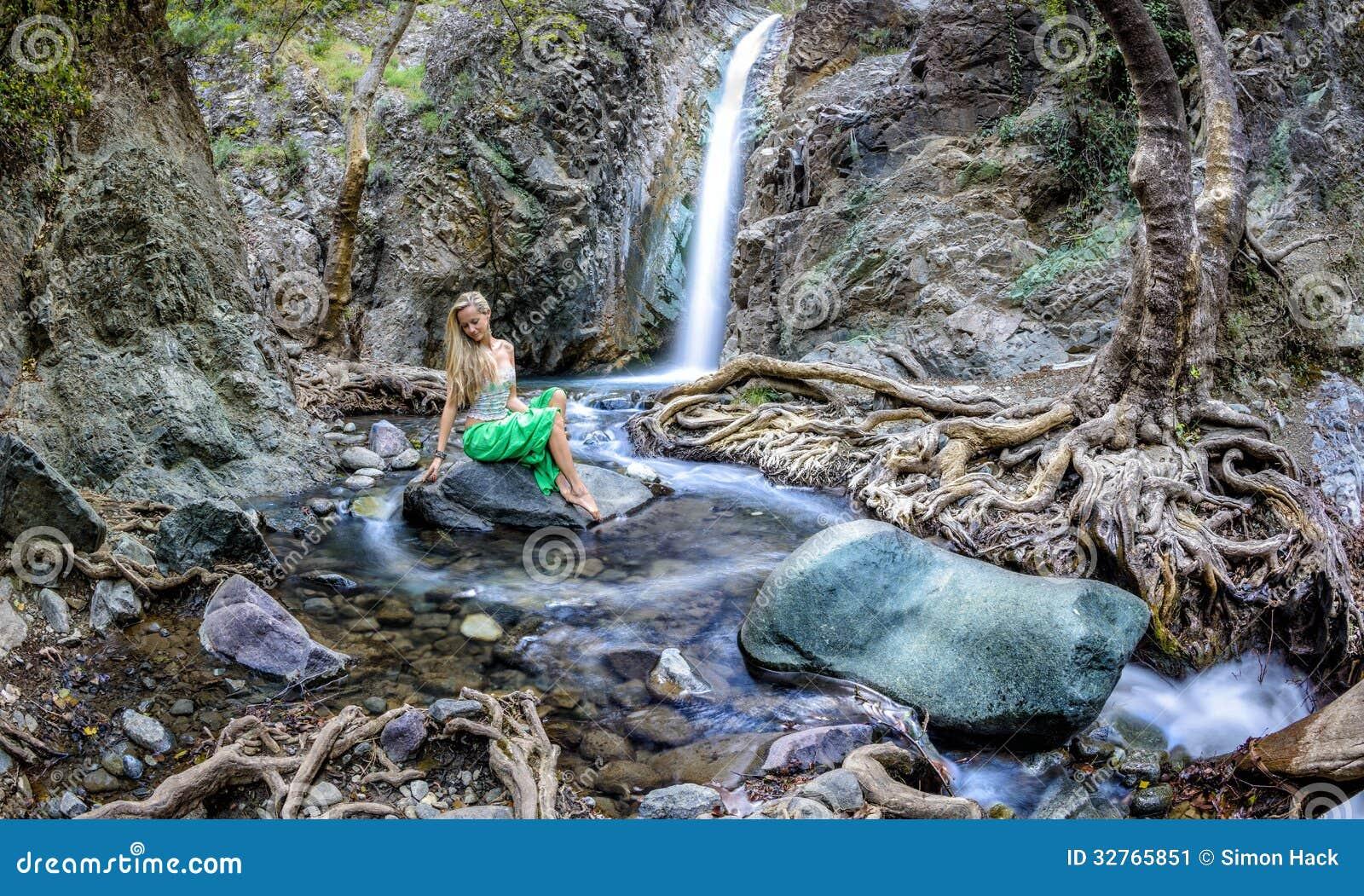 Muchacha que se sienta por las cascadas del millomeri en las montañas de los troodos