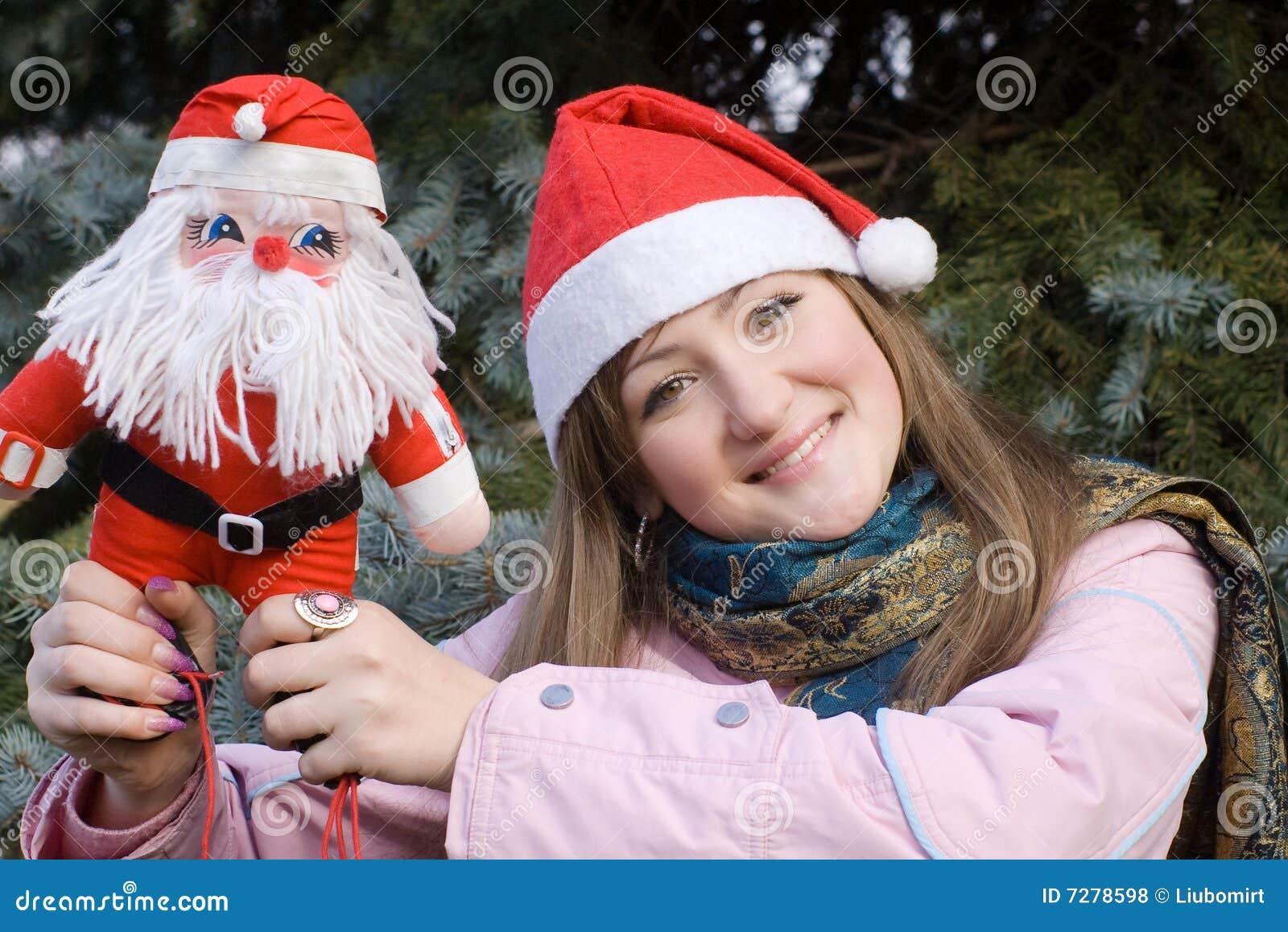 Muchacha que sonríe sosteniendo la muñeca de Santa