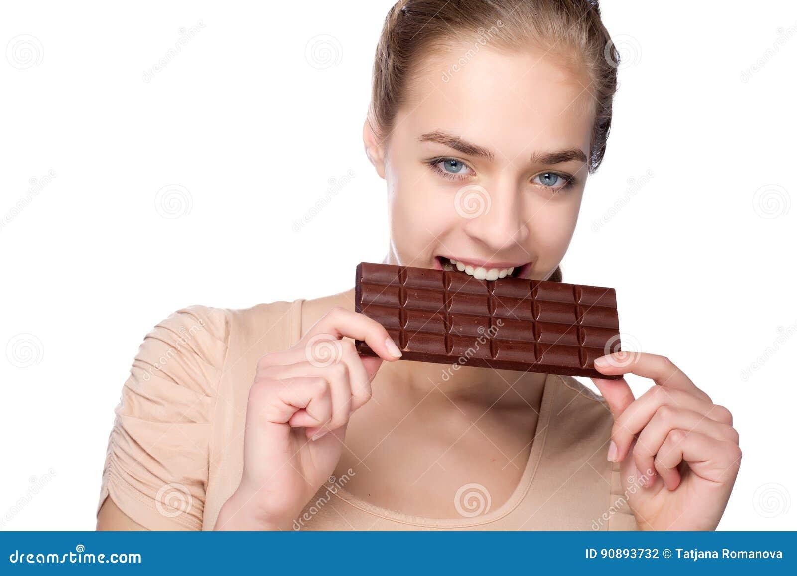 Muchacha que sostiene la barra de chocolate grande en sus tooths