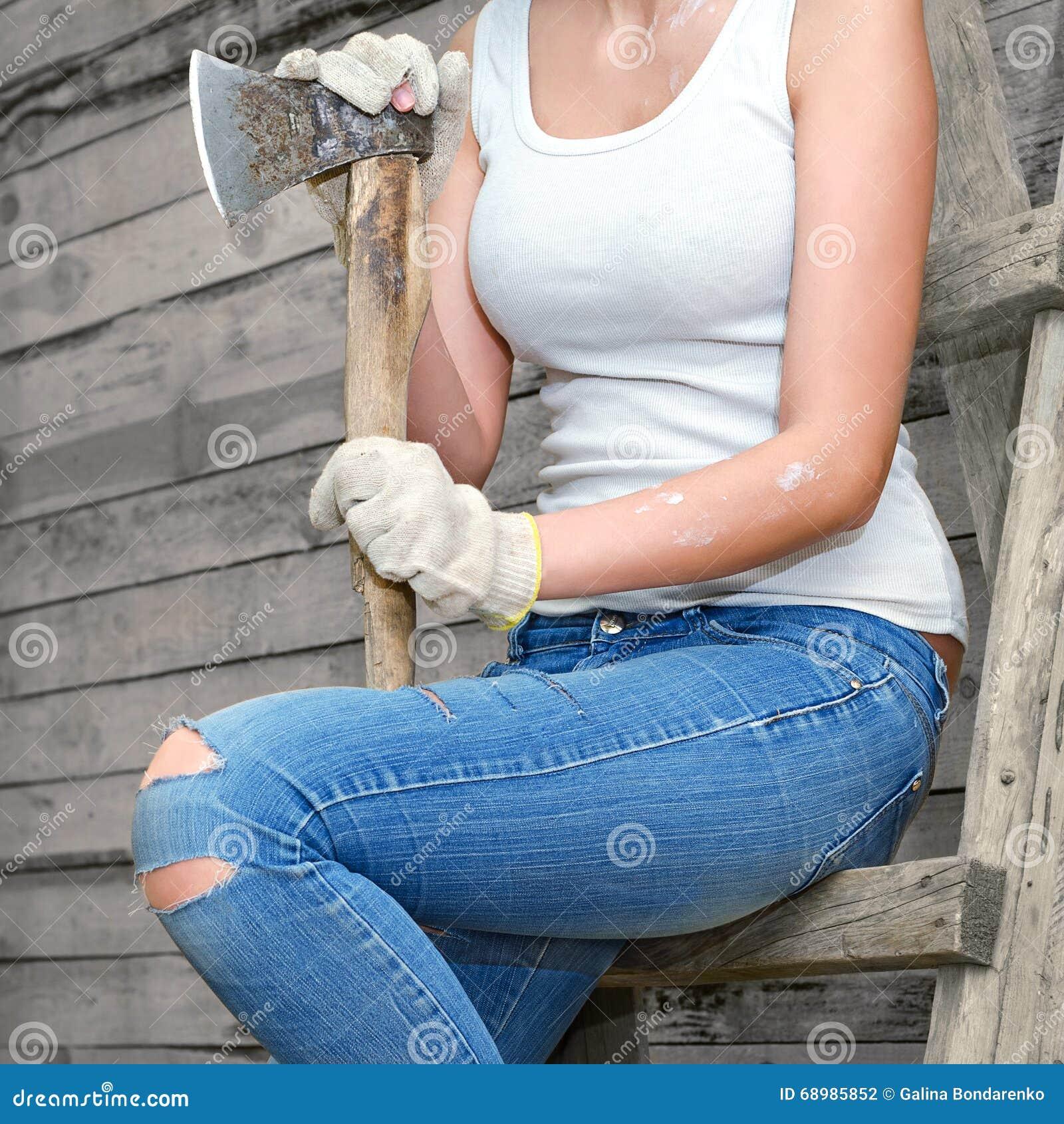 Muchacha que sostiene un hacha vieja que se sienta en las escaleras en guantes del trabajo Torso sin una cabeza