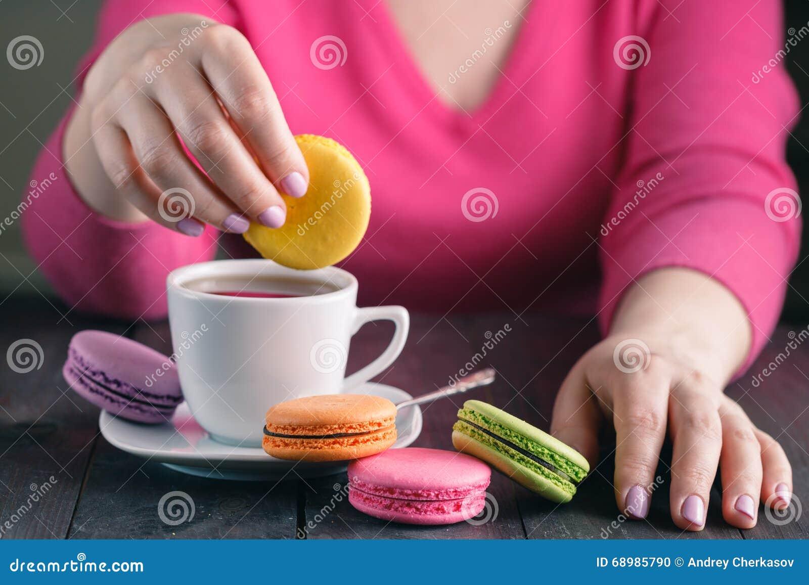 Muchacha que sostiene una taza de café con los macarrones