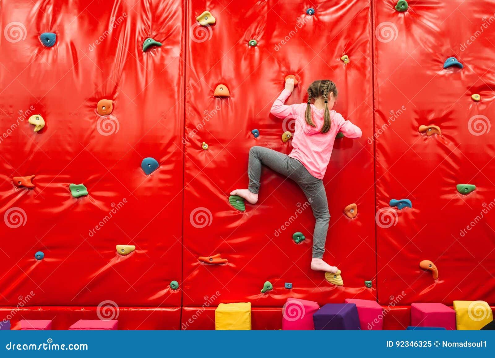 Muchacha que sube en una pared en patio de la atracción