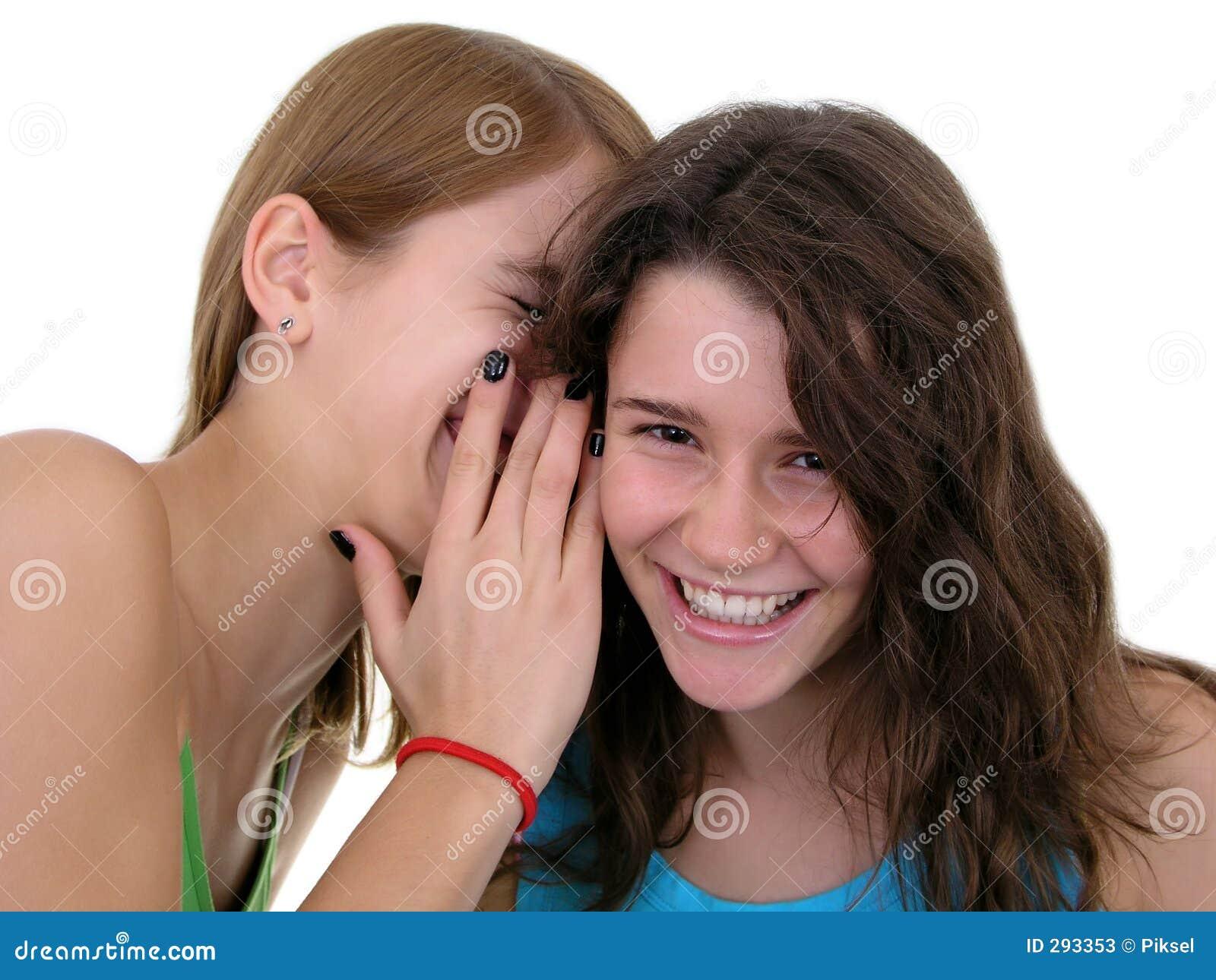 Muchacha que susurra en oído del `s del amigo