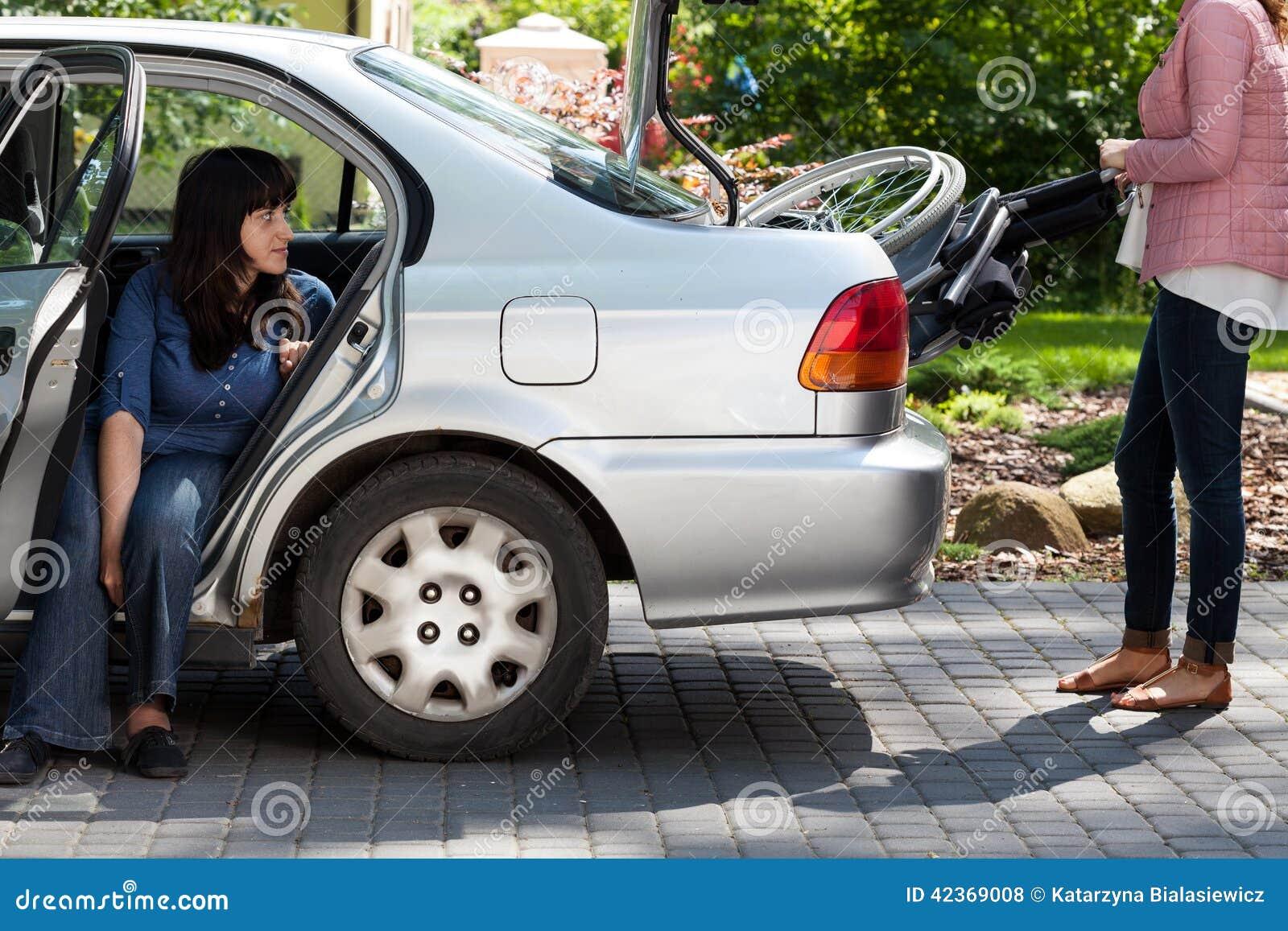 Muchacha que toma la silla de ruedas del coche