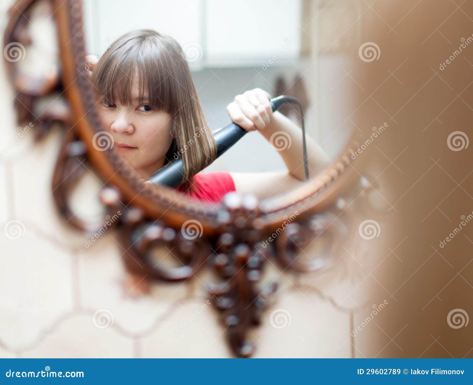 Muchacha que usa el hierro que se encrespa antes de espejo