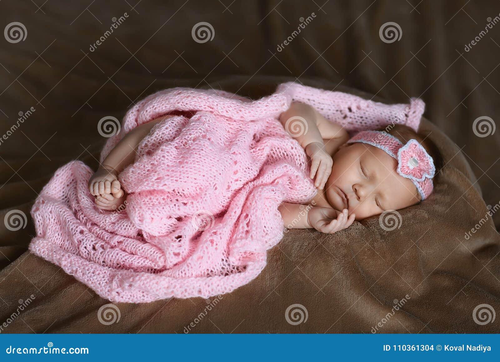 Muchacha recién nacida que está durmiendo bufanda rosada linda, suave, cubierta con las flores, las manos limpias y los pies, peq