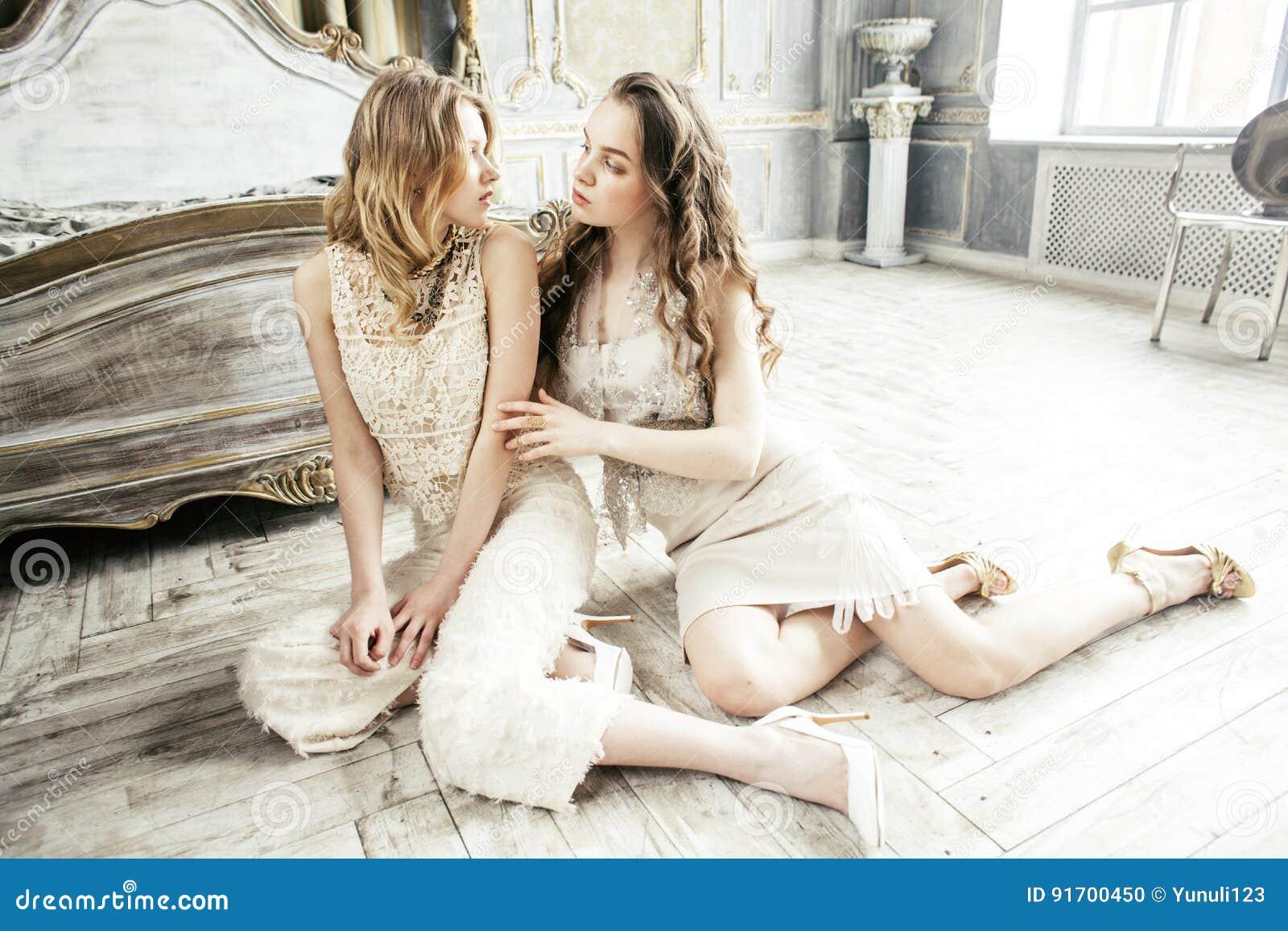 Muchacha rizada rubia del peinado de la hermana bastante gemela dos en interior de lujo de la casa junto, concepto rico de la gen
