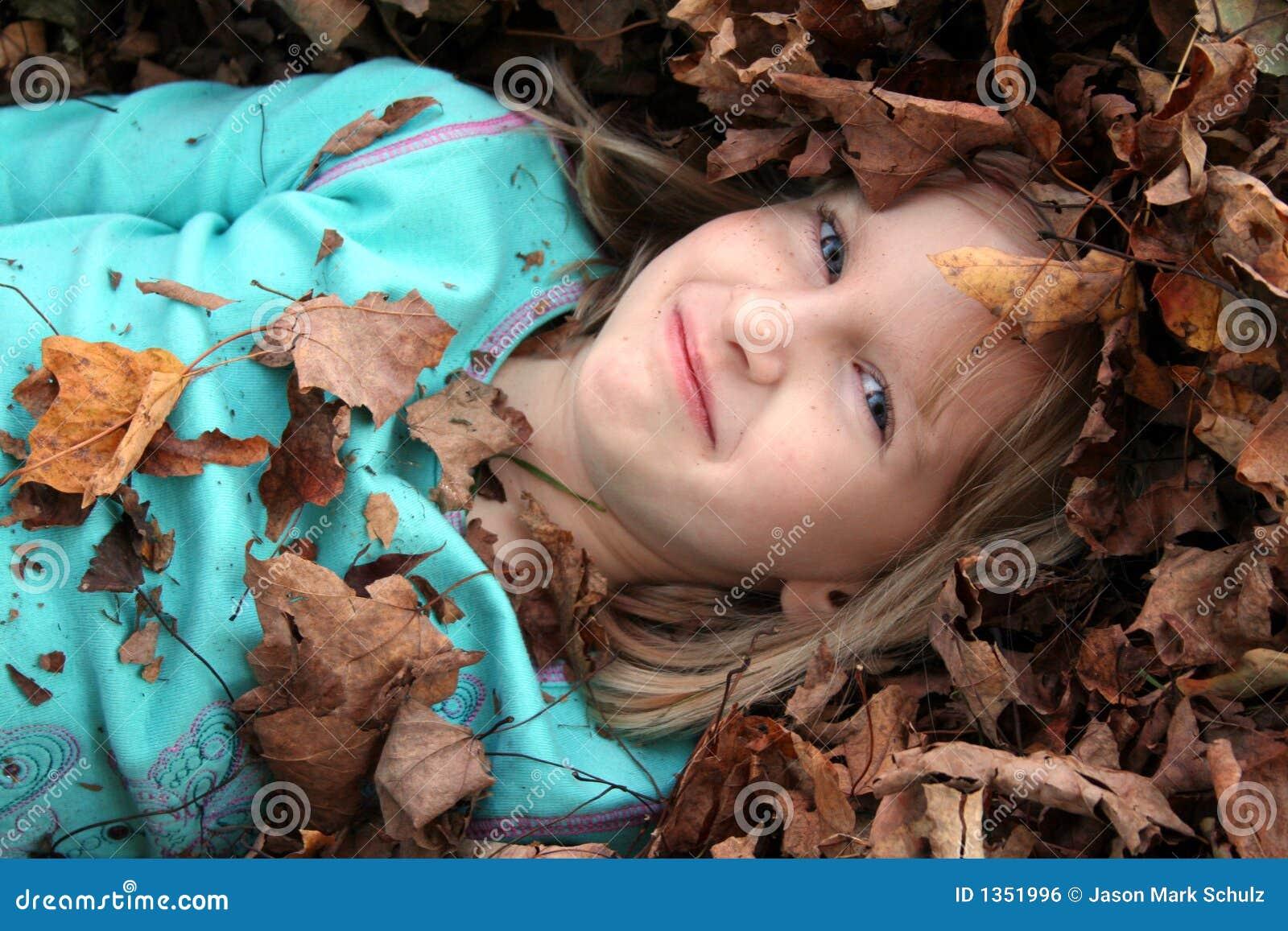 Muchacha rodeada por la pila de la hoja