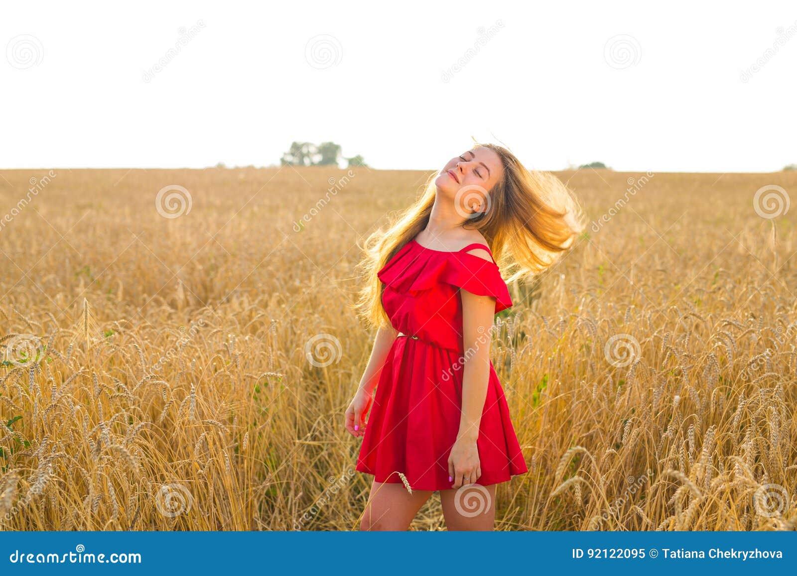 Muchacha romántica magnífica al aire libre Modelo hermoso en vestido rojo corto en campo Pelo largo que sopla en el viento Retroi